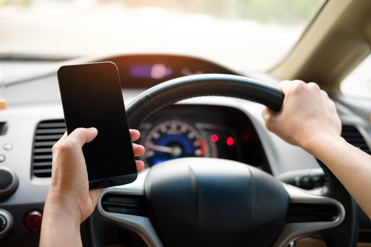 person-holding-black-smartphone-and-vehicle-steering-wheel-1028742.jpg